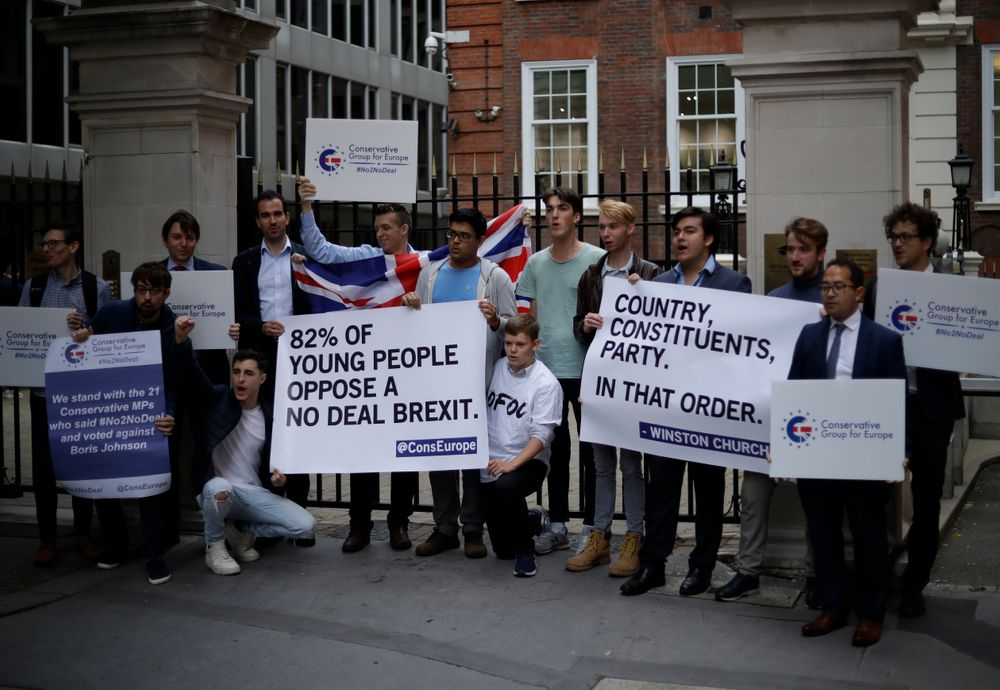Young Conservative party members hold signs as they demonstrate outside Conservative Party Campaign Headquarters in London, Wednesday, Sept. 4, 2019. With Britain's prime minister weakened by a major defeat in Parliament, defiant lawmakers were moving Wednesday to bar Boris Johnson from pursuing a