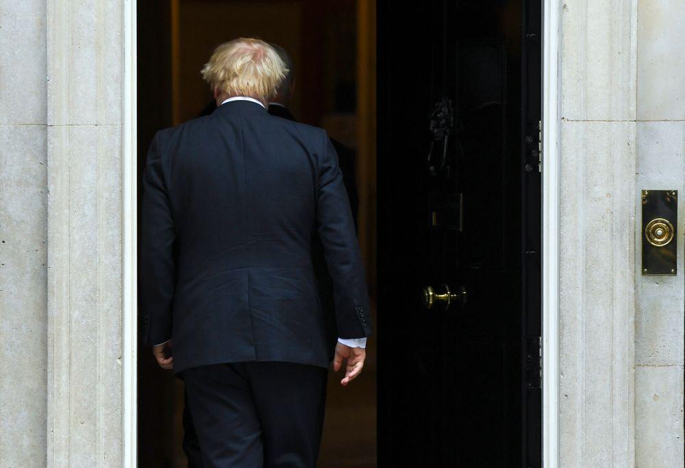 Britain's Prime Minister Boris Johnson walks back into 10 Downing Street after greeting US Vice President Mike Pence  in London, Thursday, Sept. 5, 2019. (AP Photo/Alberto Pezzali)