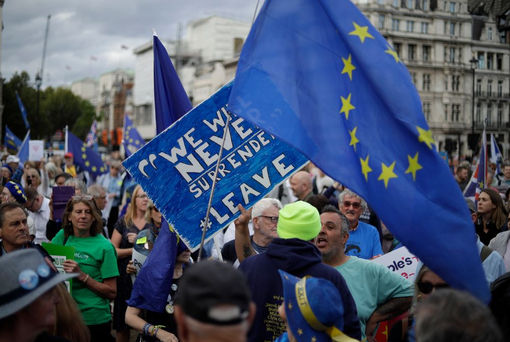A leave supporter, left holding sign, tussles with a remain supporter, right holding EU flag, during a demonstration on Parliament Square in London, Wednesday, Sept. 4, 2019. With Britain's prime minister weakened by a major defeat in Parliament, defiant lawmakers were moving Wednesday to bar Boris Johnson from pursuing a