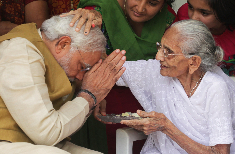 FILE - In this May 16, 2014 file photo, 90-year-old Hiraben blesses her son and India's next prime minister Narendra Modi at her home in Gandhinagar, in the western Indian state of Gujarat. Indian Prime Minister Narendra Modi's party claimed it had won re-election with a commanding lead in vote count Thursday, May 23, 2019. Modi was the third of six children born to Damodardas Modi, who ran a small tea shop at the local railway station in the tiny town of Vadnagar, in the western state of Gujarat. The family struggled to make ends meet, which meant Modi had to help his father run the shop. Modi began his political rise as a teenager in Gujarat, joining the militant Hindu organization Rashtriya Swayamsewak Sangh, which modeled itself in the 1930s after fascist Italy and which is regarded as the ideological parent of the BJP. (AP Photo/Ajit Solanki, File)