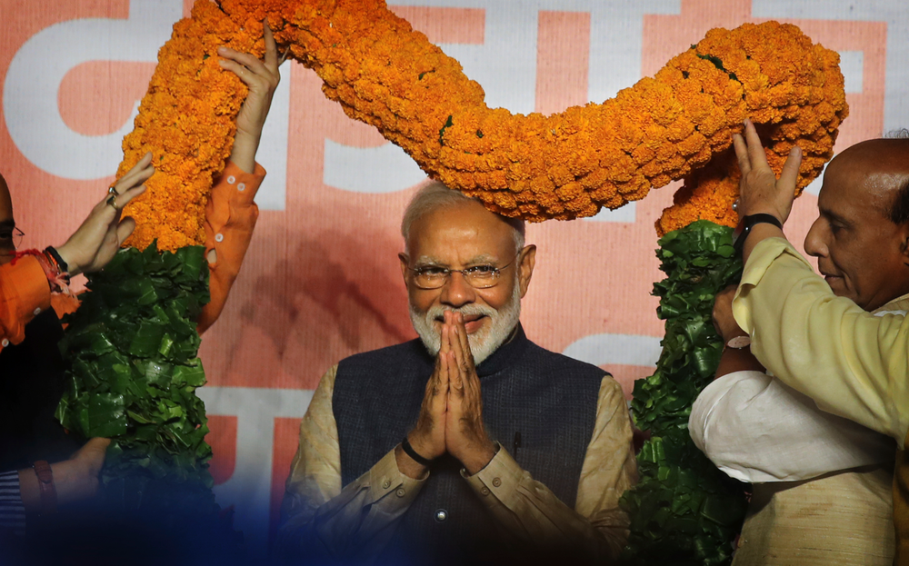 Indian Prime Minister Narendra Modi receives a giant floral garland from party leaders at their headquarters in New Delhi, India, Thursday, May 23, 2019. Indian Prime Minister Narendra Modi's party claimed it had won reelection with a commanding lead in Thursday's vote count, while the stock market soared in anticipation of another five-year term for the pro-business Hindu nationalist leader. (AP Photo/Manish Swarup)