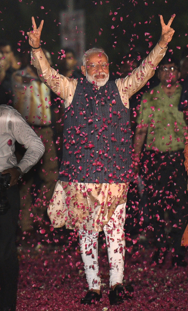 Indian Prime Minister Narendra Modi displays the victory symbol upon arrival at the party headquarters in New Delhi, India, Thursday, May 23, 2019. Modi's Hindu nationalist party claimed it won reelection with a commanding lead in Thursday's vote count, while the head of the main opposition party conceded a personal defeat that signaled the end of an era for modern India's main political dynasty. (AP Photo)