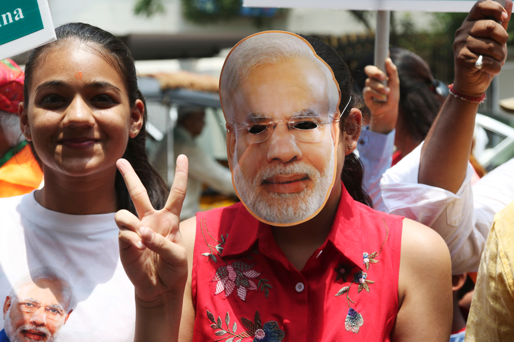 A supporter of India's ruling Bharatiya Janata Party wearing a mask of Indian Prime Minister Narendra Modi shows victory sign as they celebrate early lead in at party's state head quarter in Hyderabad, India, Thursday, May 23, 2019. Modi and his party were off to an early lead as vote counting began Thursday following the conclusion of the country's 6-week-long general election, sending the stock market soaring in anticipation of another five-year term for the Hindu nationalist leader.(AP Photo/Mahesh Kumar A.)