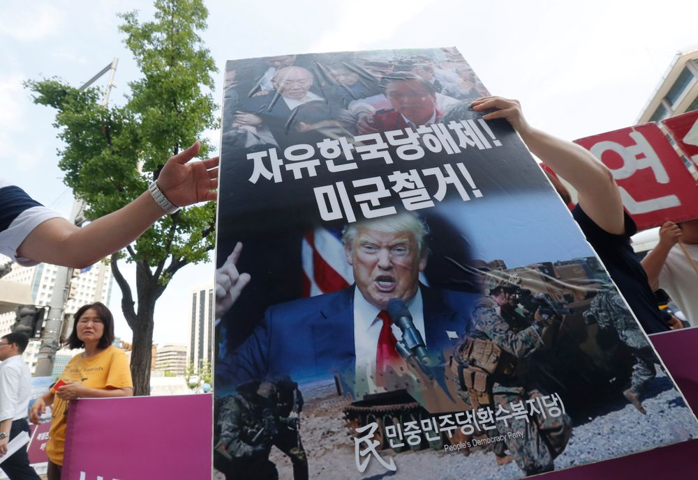 A protester carries a board during a rally to oppose a joint military exercise between South Korea and the United States near the U.S. embassy in Seoul, South Korea, Tuesday, Aug. 6, 2019. North Korea on Tuesday continued to ramp up its weapons demonstrations by firing unidentified projectiles twice into the sea while lashing out at the United States and South Korea for continuing their joint military exercises that the North says could derail fragile nuclear diplomacy. The sign reads