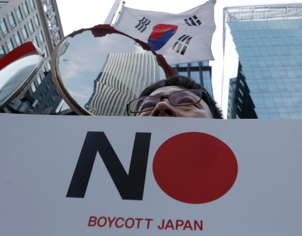 A member of the Confederation of Korean Government Employees' Unions holds a banner near the Japanese embassy in Seoul, South Korea, Tuesday, Aug. 6, 2019. South Korea's president on Monday described the country's escalating trade war with Japan as a wake-up call to revamp its economy and issued a nationalistic call for economic cooperation with North Korea, which he said would allow the Koreas to erase Japan's economic superiority in