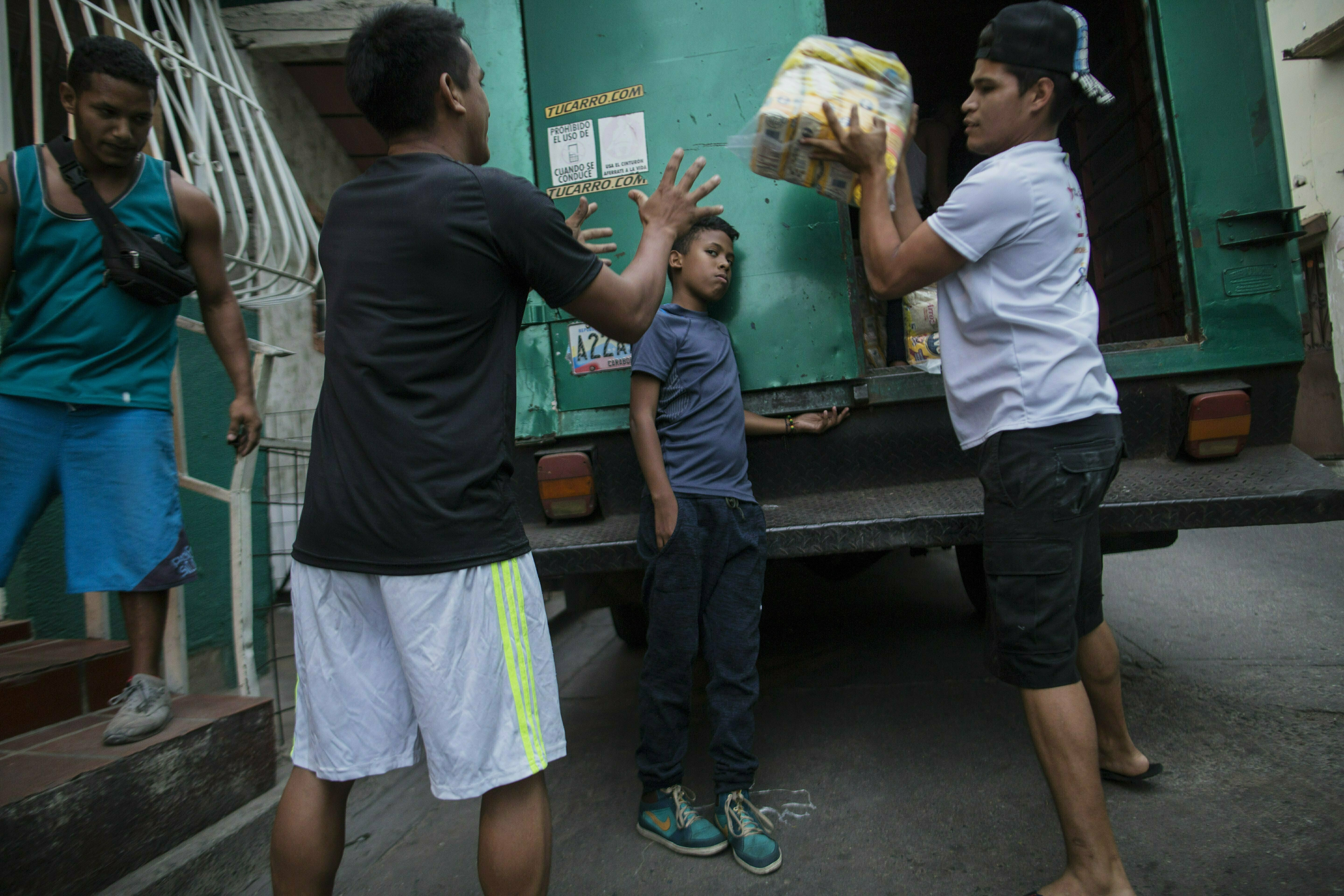 In this Jan. 31, 2019 photo, neighbors unload subsidized food distributed under a government program called