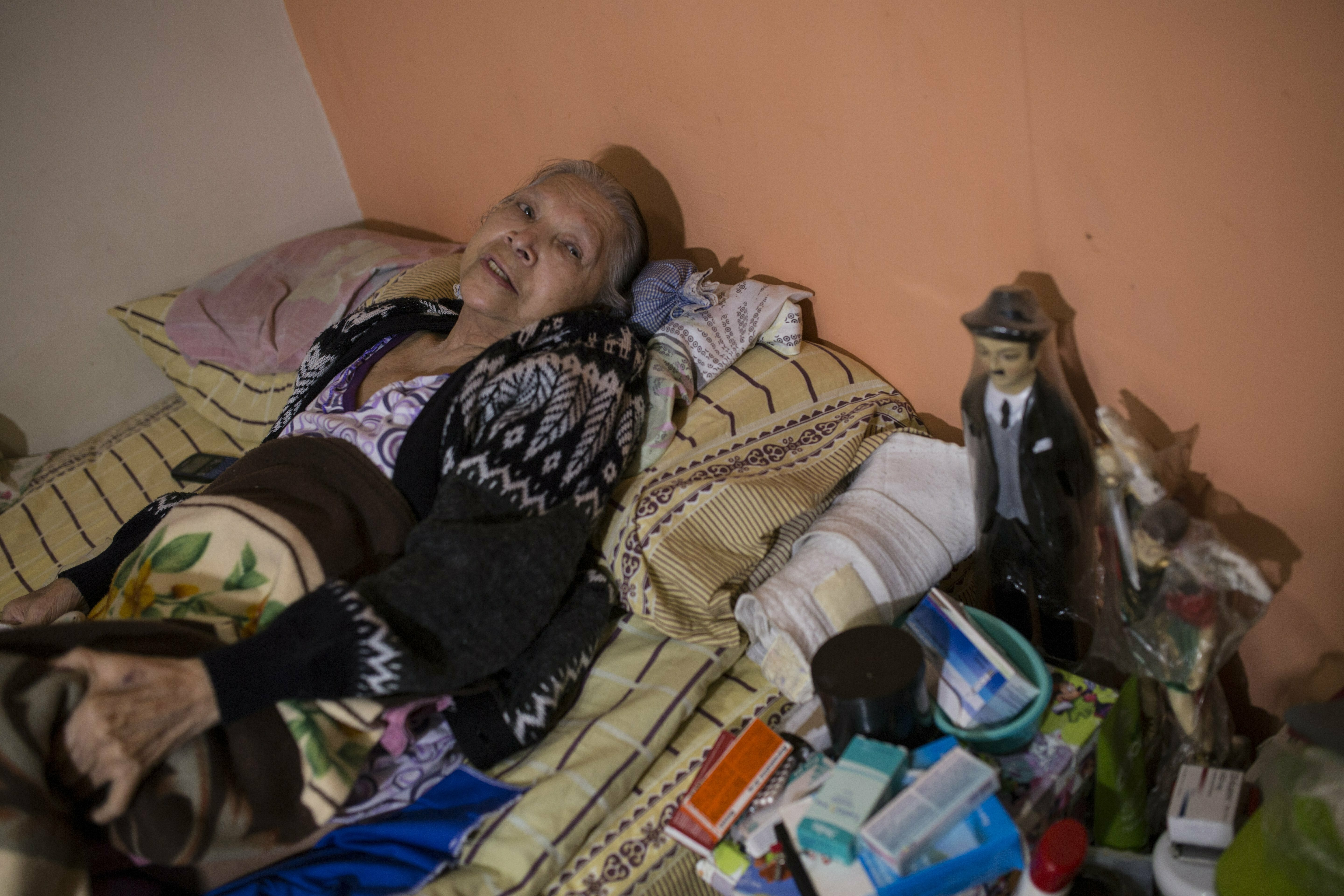 """In this Feb. 4, 2019 photo, diabetes patient Aminta Villamizar lies on her bed next to a statue of Dr. Jose Greogrio Hernandez, a 19th century Venezuelan doctor who treated the poor and is revered throughout the country as a saint, in Caracas, Venezuela. """"I was a person who worked my entire life, but this sickness destroyed me,"""" she said, complaining of joint pain and blurry vision. """"If we don't receive help, we'll have to resign ourselves to God's will."""" (AP Photo/Rodrigo Abd)"""