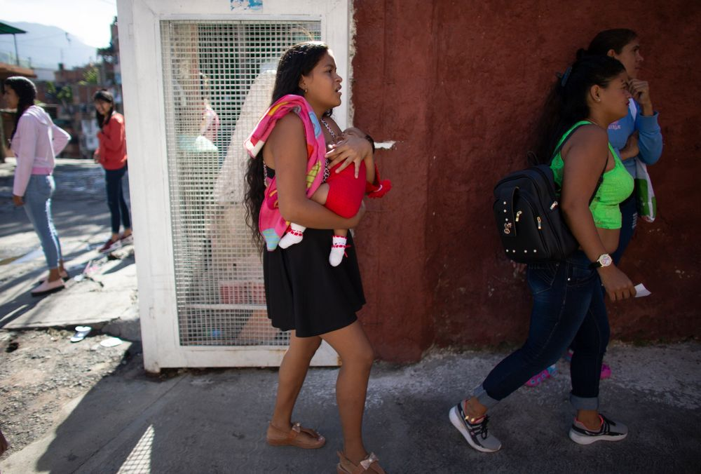 In this photo taken July 25, 2019, 15-year-old Nicol Ramirez carries her baby girl into a clinic where she hopes to get a hormonal implant to prevent future pregnancies in the Caucaguita neighborhood on the outskirts of Caracas, Venezuela. Ramírez and her sister were among the lucky few to get the last of the implants after their mom paid for a pregnancy test and they were able to prove they were not pregnant. (AP Photo/Ariana Cubillos)