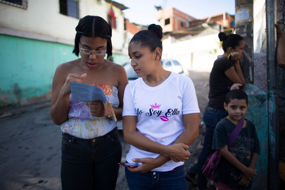 "In this photo taken July 25, 2019, young women read a brochure about hormonal implants outside a clinic where a very limited number are being administered in the Caucaguita neighborhood on the outskirts of Caracas, Venezuela. ""Women are getting pregnant and don't have options,"" said Luisa Kislinger, a women's rights activist. ""They're forced into motherhood."" (AP Photo/Ariana Cubillos)"
