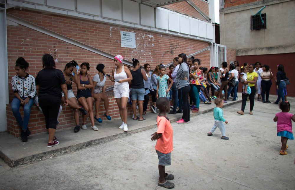 In this photo taken July 25, 2019, women with their children wait outside a clinic in hopes of getting information on the next time hormonal implants to prevent pregnancies will be available, after the clinic ran out in the Caucaguita neighborhood on the outskirts of Caracas, Venezuela. The 104 implants available were not enough for the women who wanted one. (AP Photo/Ariana Cubillos)