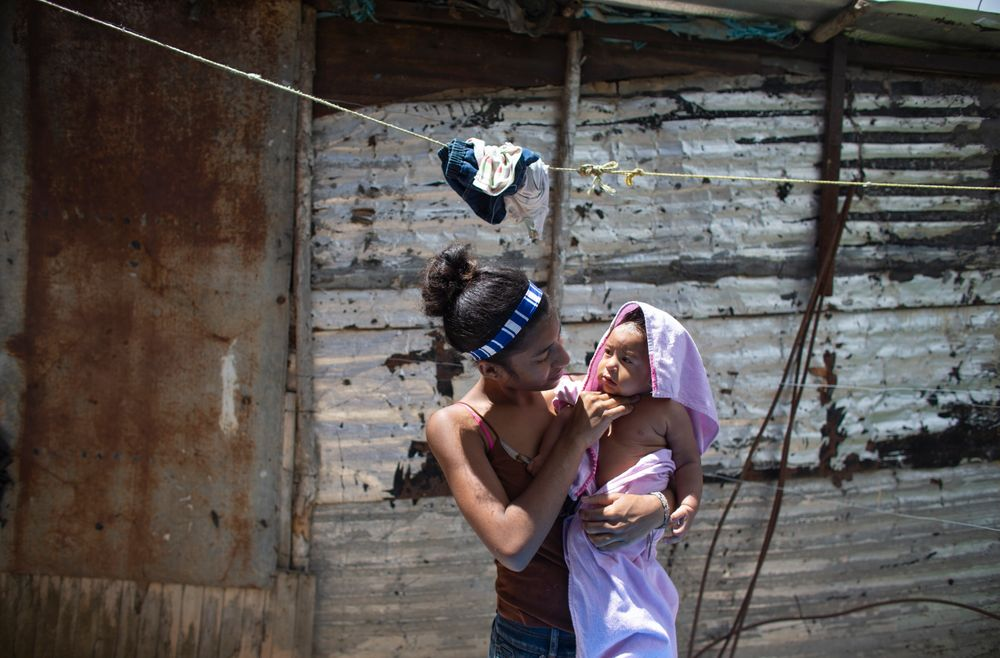 In this photo taken July 25, 2019, 15-year-old Karelys Herrera holds her baby after giving him a bath behind her home in the Caucaguita neighborhood on the outskirts of Caracas, Venezuela. Herrera said she contemplated suicide after learning she was pregnant at 14 years old. (AP Photo/Ariana Cubillos)