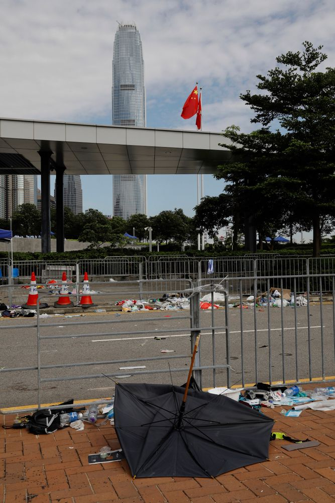 A broken umbrella left in the aftermath of Wednesday's violent protest against proposed amendments to an extradition law is seen near the Chinese flag in Hong Kong on Friday, June 14, 2019. Calm appeared to have returned to Hong Kong after days of protests by students and human rights activists opposed to a bill that would allow suspects to be tried in mainland Chinese courts. (AP Photo/Vincent Yu)
