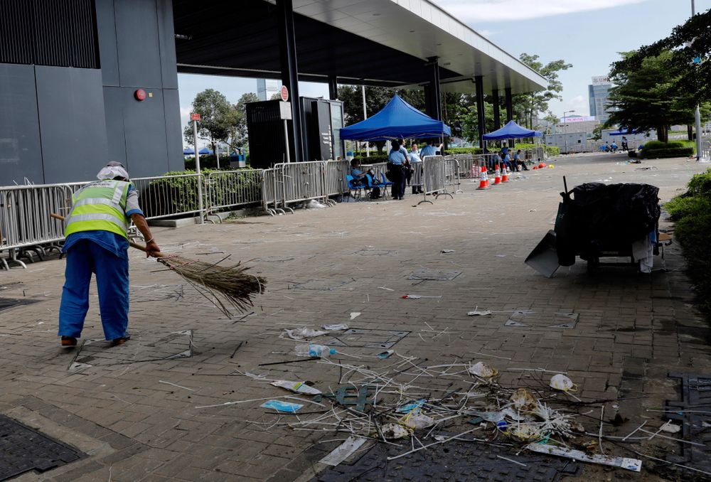 A worker cleans up in the aftermath of Wednesday's violent protest against the proposed amendments to extradition law near the Legislative Council in Hong Kong on Friday, June 14, 2019. Calm appeared to have returned to Hong Kong after days of protests by students and human rights activists opposed to a bill that would allow suspects to be tried in mainland Chinese courts. (AP Photo/Vincent Yu)
