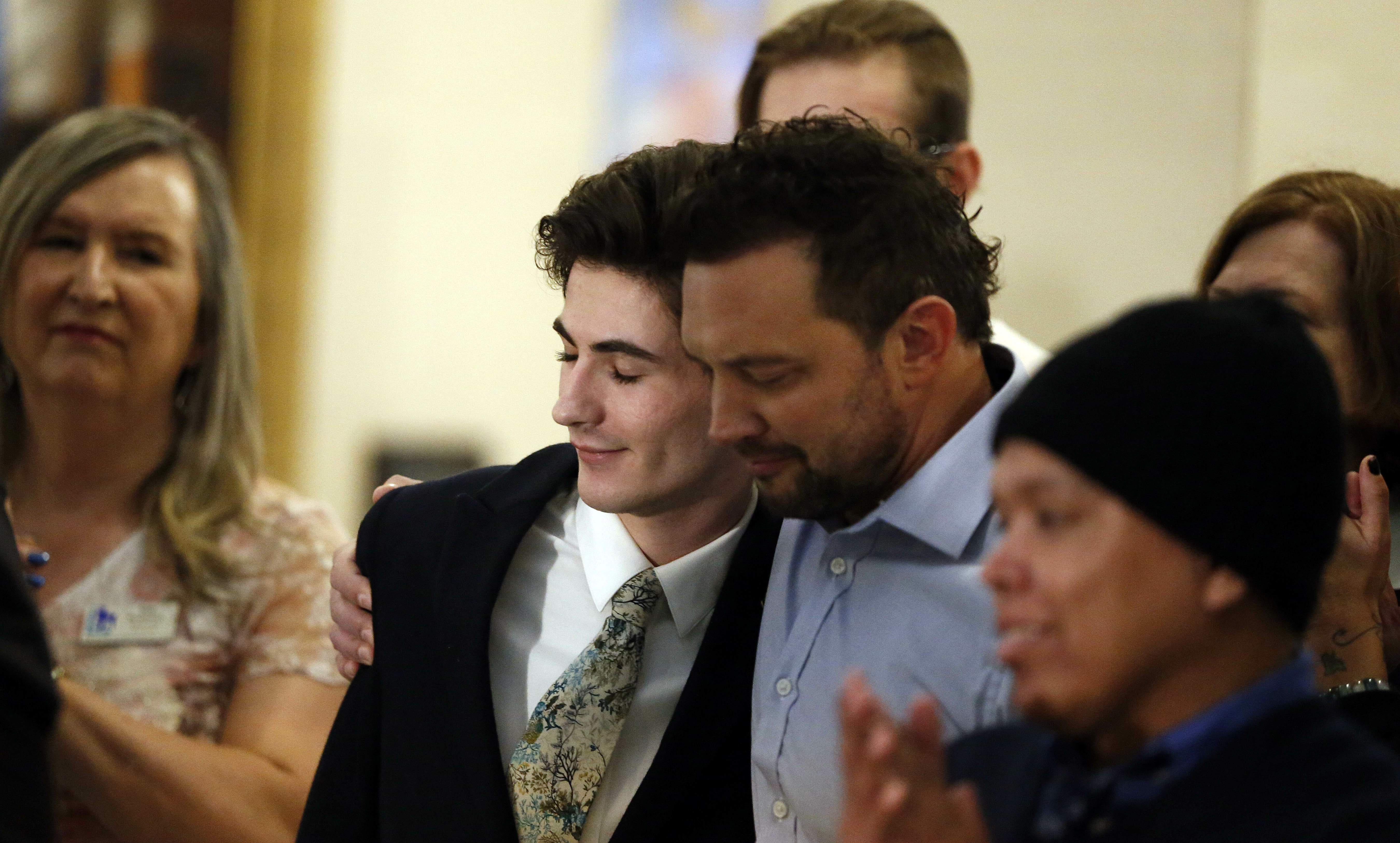 Nathan Dalley, center, receives a hug after speaking during a news conference at the Utah State Capitol Thursday, Feb. 21, 2019, in Salt Lake City. Two Republican lawmakers proposed a ban on gay conversion therapy for minors in conservative Utah on Thursday, a plan that's been hailed as a milestone by advocates and won't be opposed by the influential Mormon church. Those who have been through conversion therapy, like 19-year-old Dalley, say it leaves them depressed and can lead to suicide attempts. (AP Photo/Rick Bowmer)