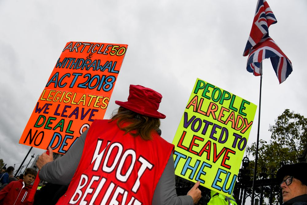 Pro Brexit demonstrators gather outside the Houses of Parliament holding placards and waving Union Flags in London, Monday, Oct. 21, 2019. The European Commission says the fact that British Prime Minister Boris Johnson did not sign a letter requesting a three-month extension of the Brexit deadline has no impact on whether it is valid and that the European Union is considering the request. (AP Photo/Alberto Pezzali)