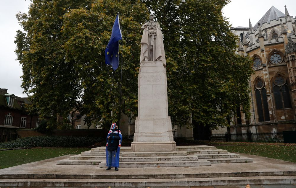 A lone anti-Brexit protester demonstrates in front of a statue to former British monarch George V next to Westminster Abbey in London, Monday, Oct. 21, 2019.  The European Commission says the fact that British Prime Minister Boris Johnson did not sign a letter requesting a three-month extension of the Brexit deadline has no impact on whether it is valid and that the European Union is considering the request. (AP Photo/Alastair Grant)