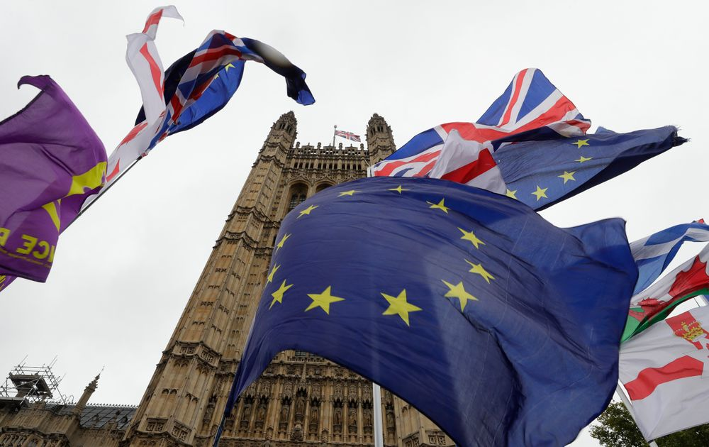 A confusion of various flags fly outside Parliament in London, Monday, Oct. 21, 2019.  The European Commission says the fact that British Prime Minister Boris Johnson did not sign a letter requesting a three-month extension of the Brexit deadline has no impact on whether it is valid and that the European Union is considering the request. (AP Photo/Kirsty Wigglesworth)