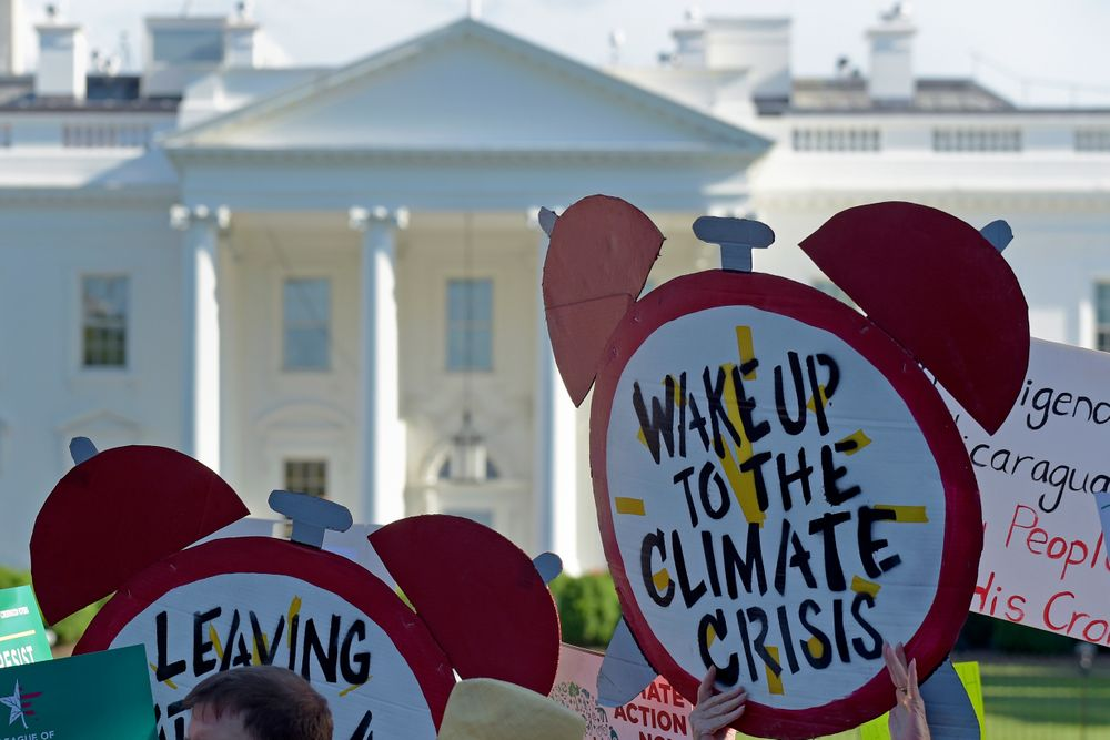 FILE- In this June 1, 2017 file photo, protesters gather outside the White House in Washington to protest President Donald Trump's decision to withdraw the Unites States from the Paris climate change accord.  For more than two years President Trump has talked about pulling the United States out of the landmark Paris climate agreement. Starting Monday, he can finally do something about it. But the withdrawal process will take a year and doesn't become official until the day after the 2020 presidential election. And if someone other than Trump wins in 2020, the next president can get back in the deal in just 30 days.  (AP Photo/Susan Walsh)