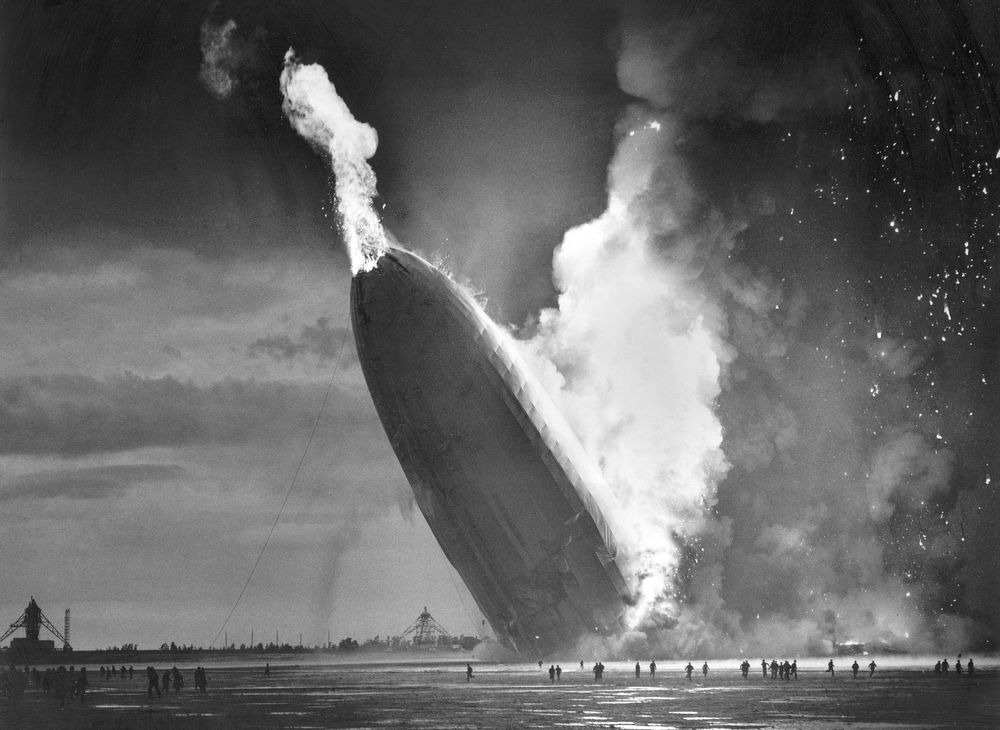 FILE - In this May 6, 1937 file photo, the German dirigible Hindenburg crashes to earth in flames after exploding at the U.S. Naval Station in Lakehurst, N.J. Werner Gustav Doehner, the last survivor of the disaster, died Nov. 8, 2019 at age 90 in Laconia, N.H. Doehner was 8-years old when he boarded the zeppelin in Germany with his parents and older siblings to return from a vacation. (AP Photo/Murray Becker, File)