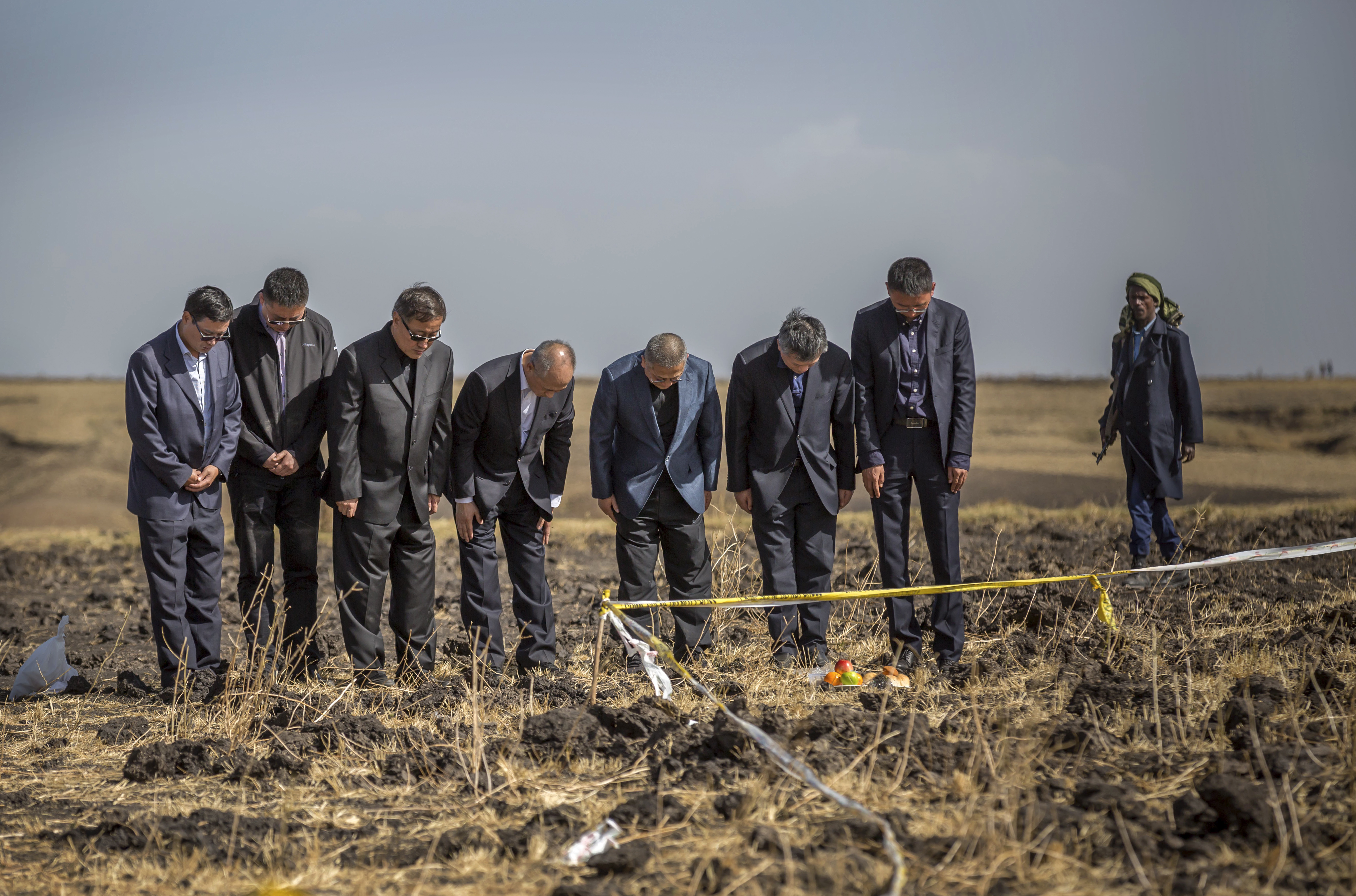 Officials from the Aviation Industry Corporation of China (AVIC) pray next to an offering of fruit, bread rolls, and a plastic container of Ethiopian Injera, a fermented sourdough flatbread, placed next to incense sticks, at the scene where the Ethiopian Airlines Boeing 737 Max 8 crashed shortly after takeoff on Sunday killing all 157 on board, near Bishoftu, or Debre Zeit, south of Addis Ababa, in Ethiopia Tuesday, March 12, 2019. Ethiopian Airlines had issued no new updates on the crash as of late afternoon Tuesday as families around the world waited for answers, while a global team of investigators began picking through the rural crash site. (AP Photo/Mulugeta Ayene)
