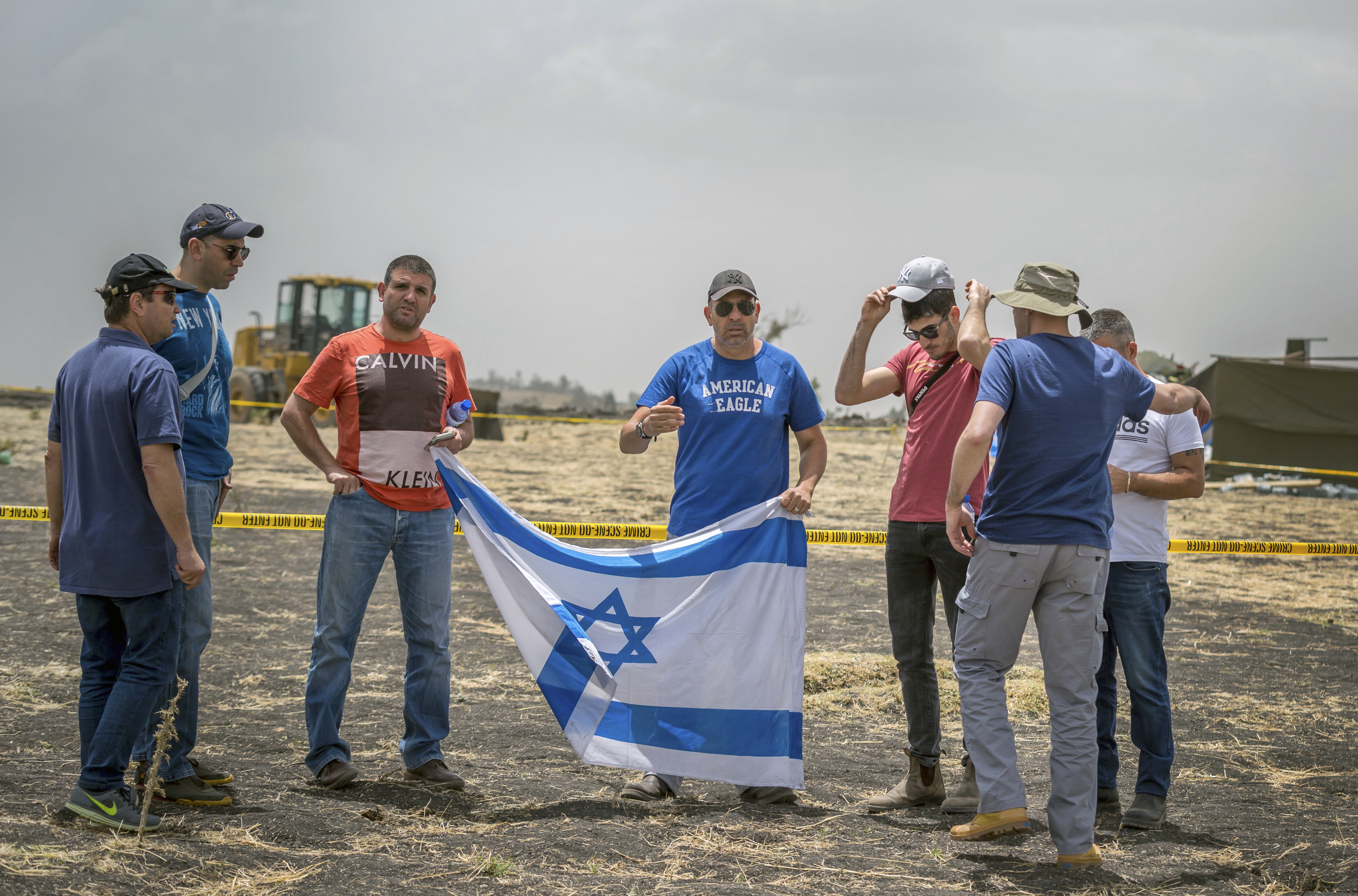 Israeli relatives hold their national flag at the scene where the Ethiopian Airlines Boeing 737 Max 8 crashed shortly after takeoff on Sunday killing all 157 on board, near Bishoftu, south-east of Addis Ababa, in Ethiopia Thursday, March 14, 2019. Flight recorders from the doomed Ethiopian Airlines flight arrived in France for analysis Thursday as frustrated relatives of the 157 people killed stormed out of a meeting with airline officials in Addis Ababa. (AP Photo/Mulugeta Ayene)