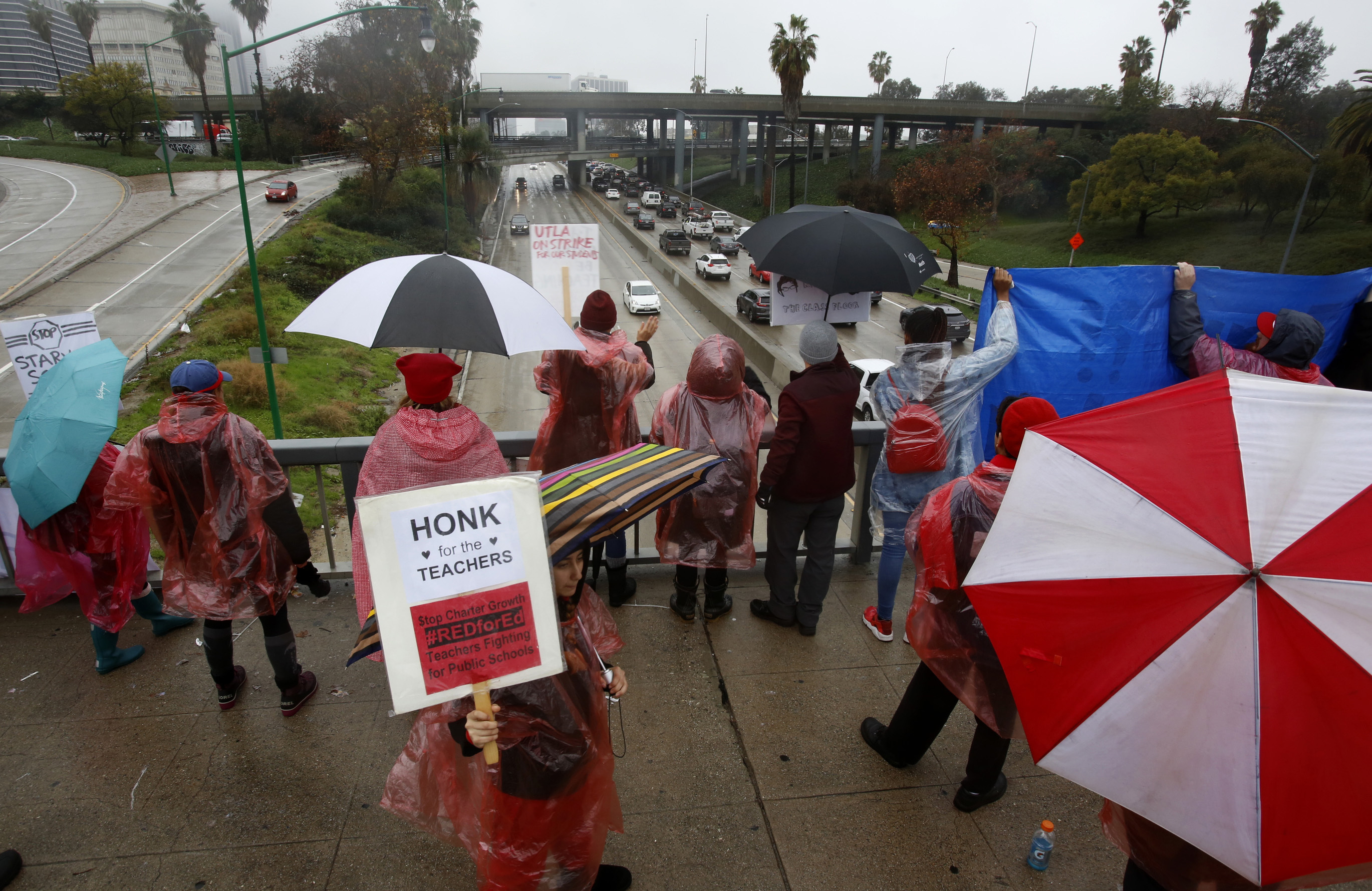 Los Angeles Unified School District educators picket over the Harbor Freeway downtown Los Angeles Thursday, Jan. 17, 2019. A new round of contract negotiations began between Los Angeles school district officials and a teachers union as thousands of educators picketed in the rain. The announcement that the two sides were sitting down Thursday for the first time in nearly a week didn't indicate whether any new contract offers would be on the table. Union officials tempered expectations, saying a quick deal was unlikely. District officials have said teacher demands could bankrupt the school system.  (AP Photo/Damian Dovarganes)