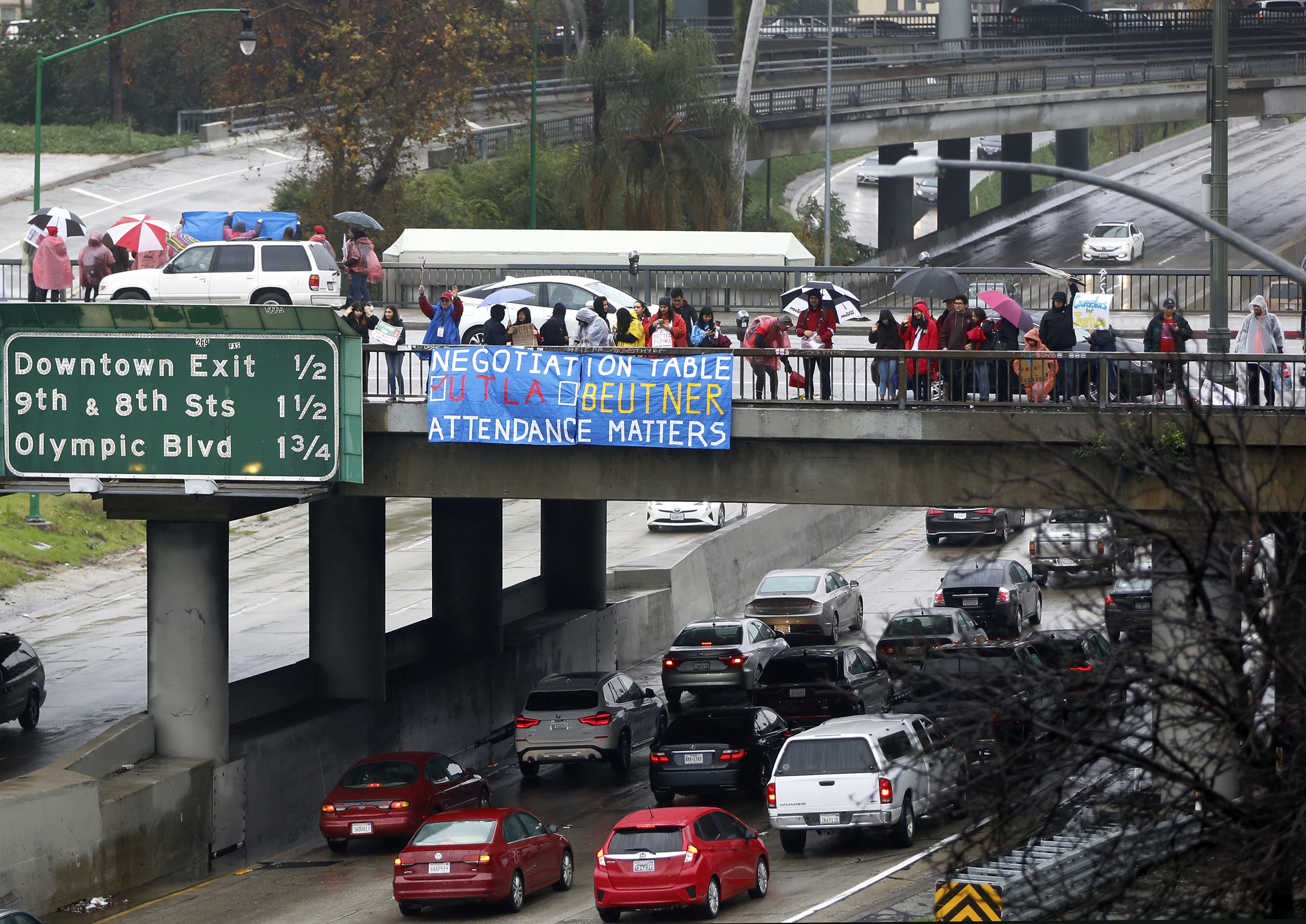 Teachers, parents and children picket despite heavy rain drenching downtown Los Angeles Thursday, Jan. 17, 2019. A new round of contract negotiations began between Los Angeles school district officials and a teachers union as thousands of educators picketed in the rain. The announcement that the two sides were sitting down Thursday for the first time in nearly a week didn't indicate whether any new contract offers would be on the table. Union officials tempered expectations, saying a quick deal was unlikely. District officials have said teacher demands could bankrupt the school system.  (AP Photo/Damian Dovarganes)