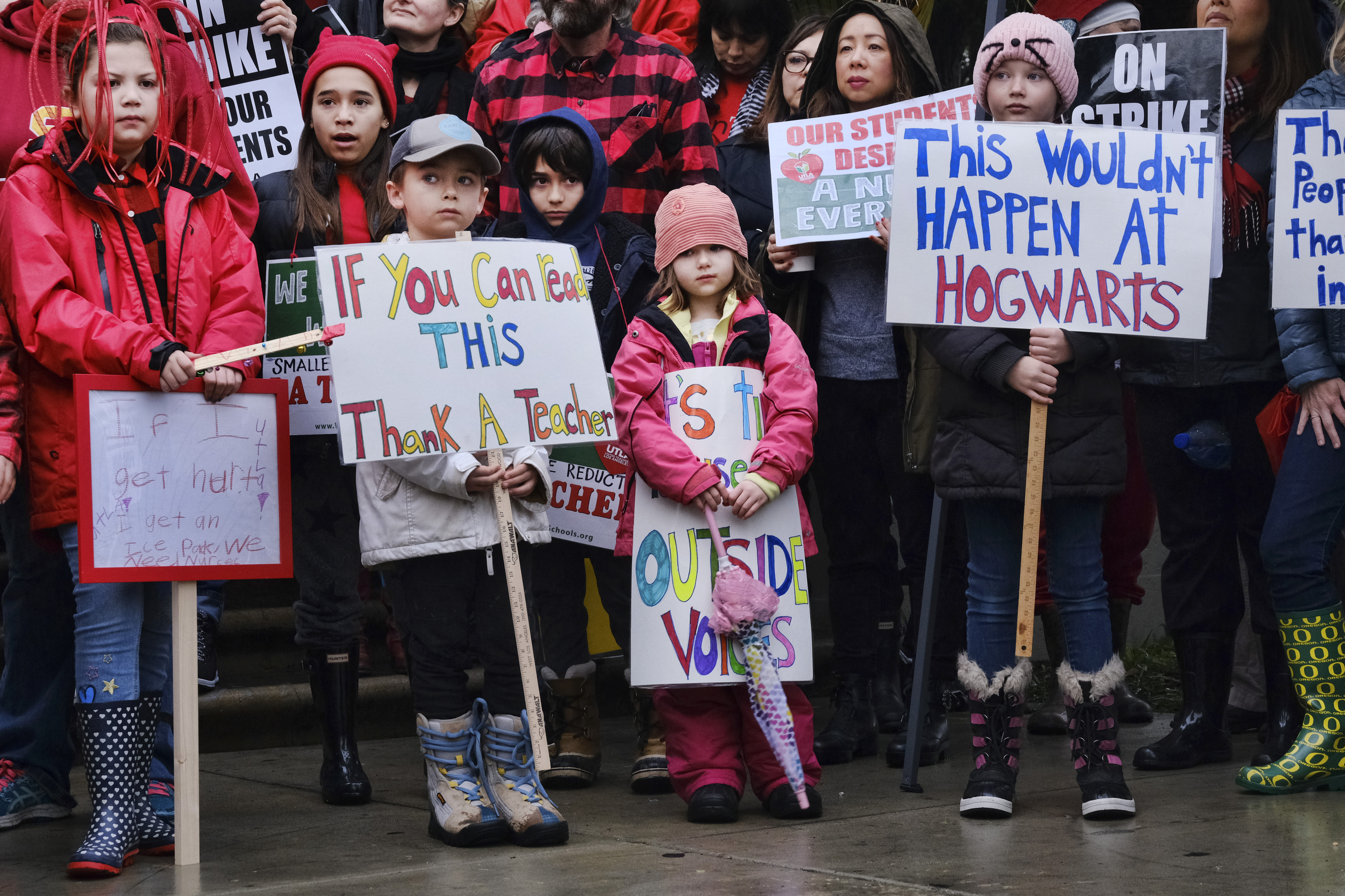 Elementary students, from right, Sawyer Mack is joined by his sisters, Capri and Kaya in support of a teachers strike in front of Hamilton High School  in Los Angeles on Wed. Jan. 16, 2019. Los Angeles school administrators urged the union to resume bargaining as tens of thousands of teachers planned to walk picket lines for a third day Wednesday, after being joined on strike for the first time by some of their counterparts from independent charter schools. (AP Photo/Richard Vogel)