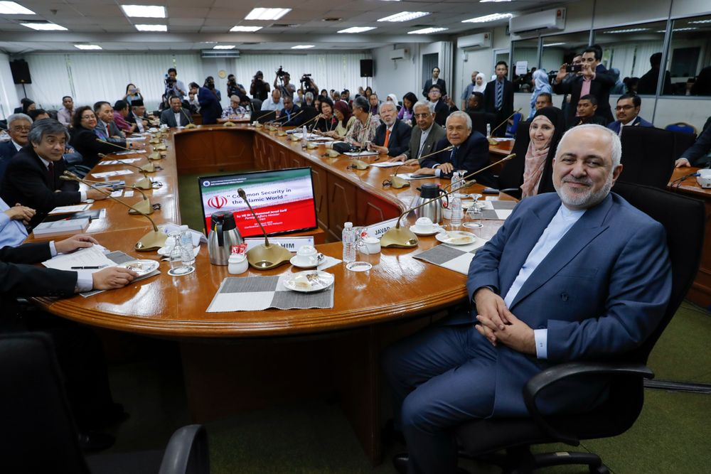Iranian Foreign Minister Mohammad Javad Zarif, right, smile as he arrives for a forum titled