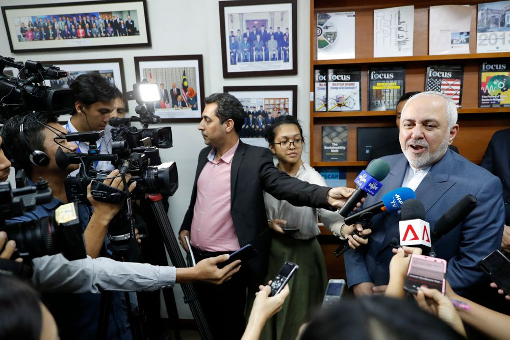 Iranian Foreign Minister Mohammad Javad Zarif, right, speaks to reporters after a forum titled