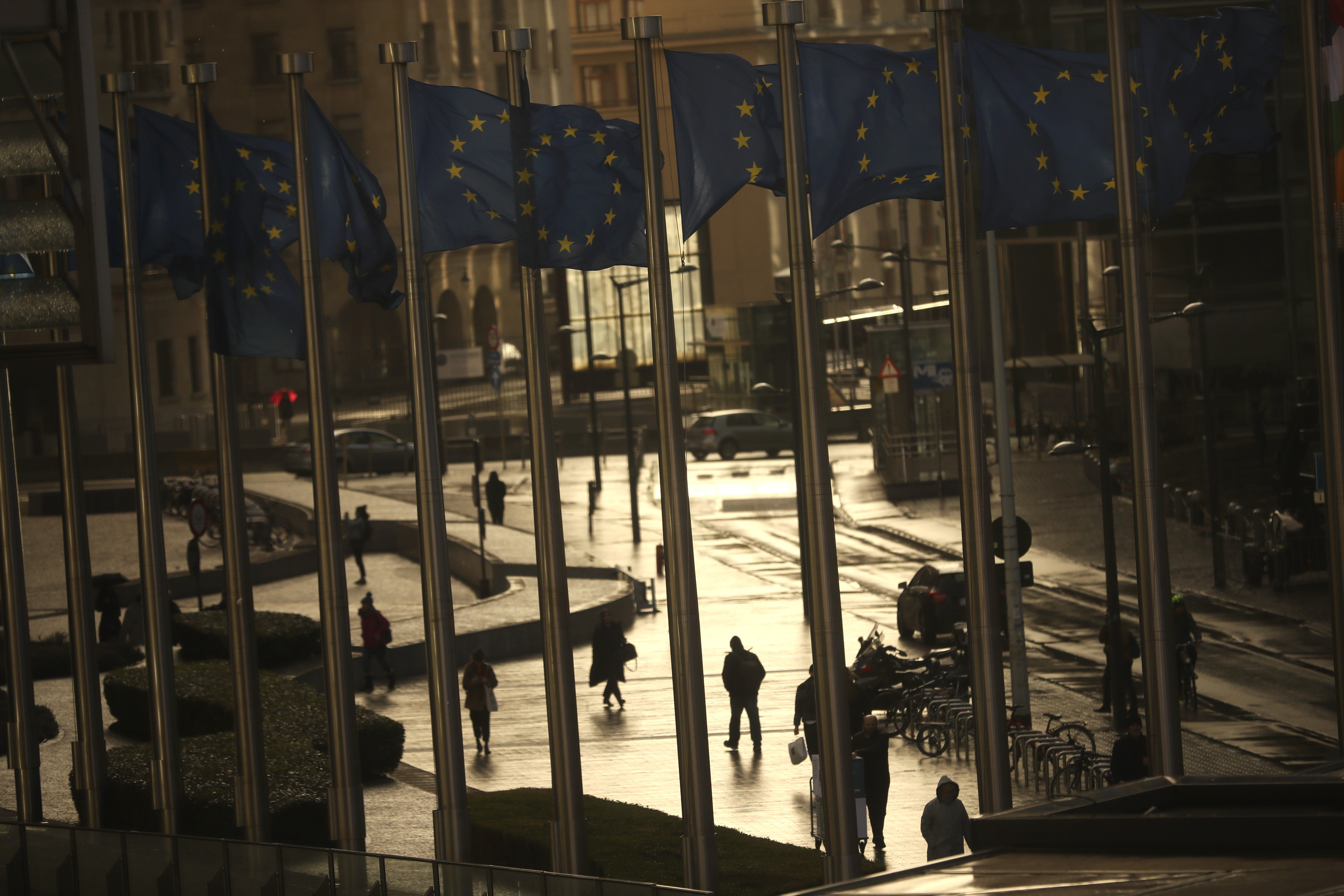 Commuters walk past European Union flags outside the European Commission headquarters in Brussels, Thursday, March 7, 2019. Brexit negotiations between Britain with the European Union will continue through the weekend, the country's chief law officer said Thursday as the U.K. scrambled to secure changes to the divorce deal before a vote in Parliament next week. (AP Photo/Francisco Seco)