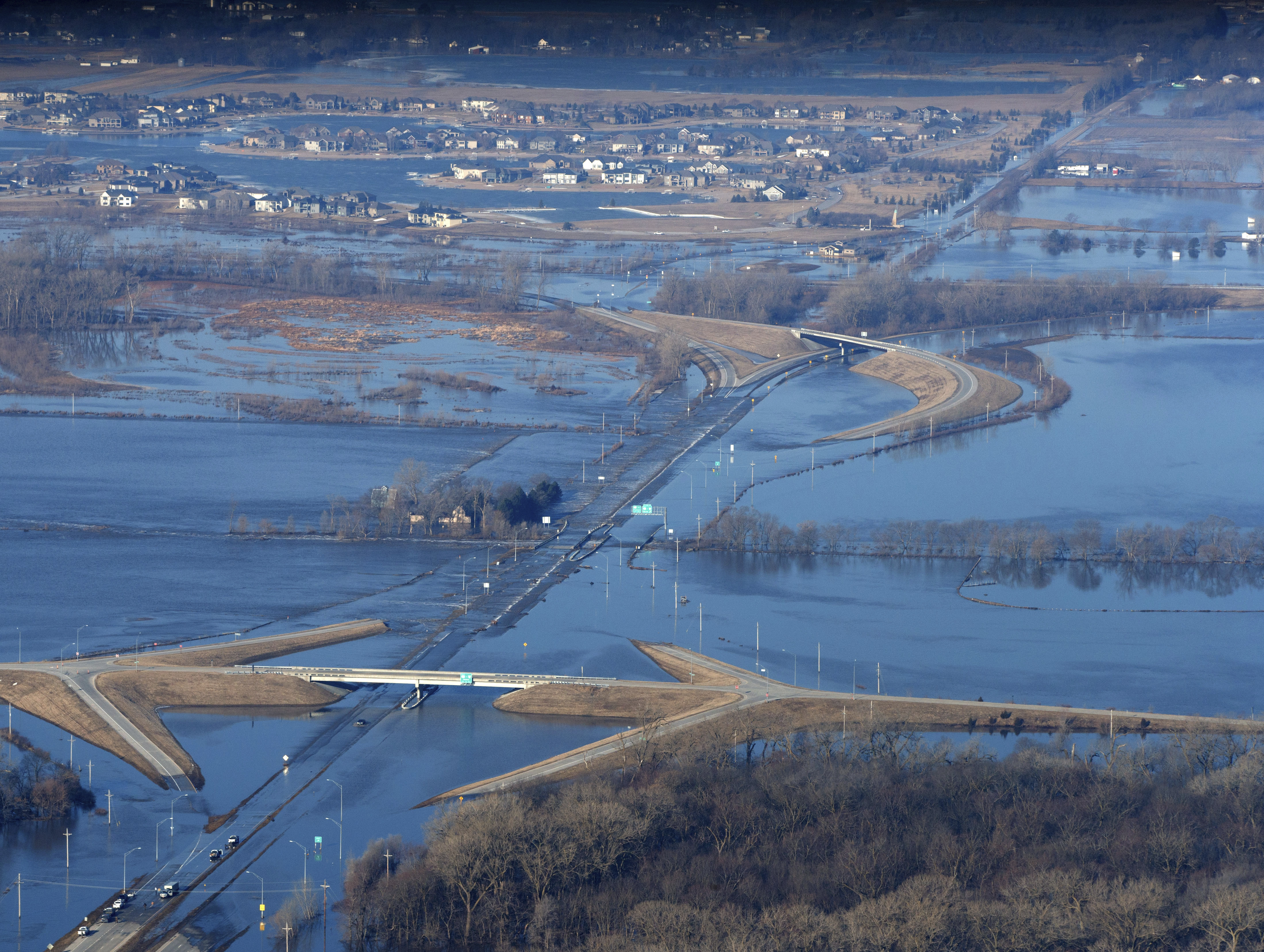 CORRECTS MONTH TO MARCH NOT MAY - The Elkhorn River consumes a section of western Douglas County Sunday, March 17, 2019, in Omaha, Neb. Hundreds of people were evacuated from their homes in Nebraska and Iowa as levees succumbed to the rush of water. (Jeff Bundy/Omaha World-Herald via AP)