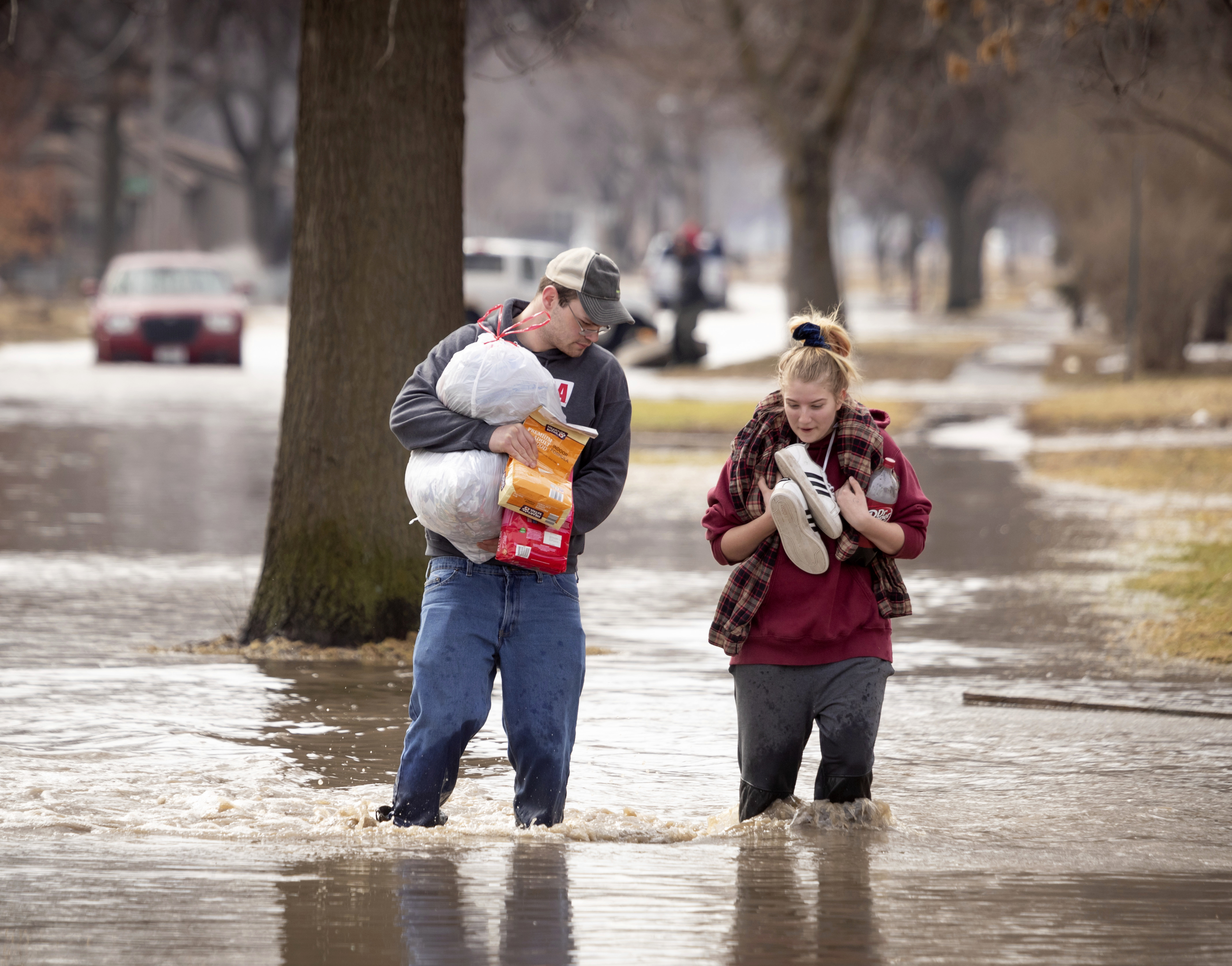 CORRECTS MONTH TO MARCH NOT MAY - Anthony Thomson, left, and Melody Walton make their way out of a flooded neighborhood Sunday, March 17, 2019, in Fremont, Neb. Hundreds of people were evacuated from their homes in Nebraska and Iowa as levees succumbed to the rush of water. (Kent Sievers/Omaha World-Herald via AP)