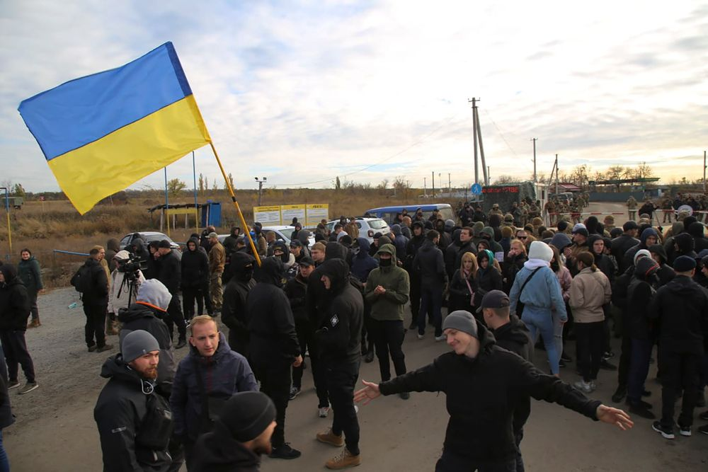 Ukrainian army veterans and volunteers wave the national flag at a checkpoint near the village of Zolote in the Luhansk region, Ukraine, Wednesday, Oct. 9, 2019.  Several dozen activists arrived on Wednesday in the area of a much anticipated pullback of heavy weaponry from both sides of the de facto border, saying that they would try to prevent it from happening. (AP Photo/Bohdan Kutepov)