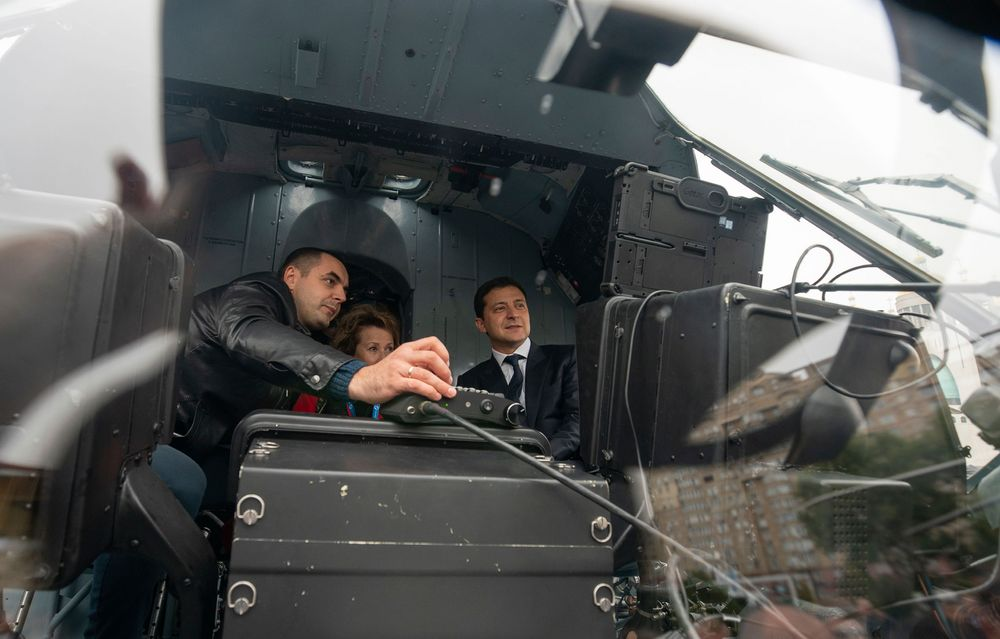 In this handout photo provided by the Ukrainian Presidential Press Office, Ukrainian President Volodymyr Zelenskiy, right, sits inside a military helicopter as he visits an arm exhibition in Kyiv, Ukraine, Wednesday, Oct. 9, 2019. (Ukrainian Presidential Press Office via AP)