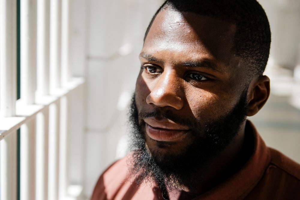 """In this Thursday, Aug. 29, 2019 photo incarcerated filmmaker Donyea poses for a portrait at the State Correctional Institution in Chester, Pa.  Eastern State Penitentiary, a former prison that's now a museum in Philadelphia is showcasing the work of currently incarcerated filmmakers, projecting the animated shorts onto its outside walls. The new exhibit titled """"Hidden Lives Illuminated"""" offers a glimpse into the lives of these inmates to passersby and museum visitors alike.  (AP Photo/Matt Rourke)"""