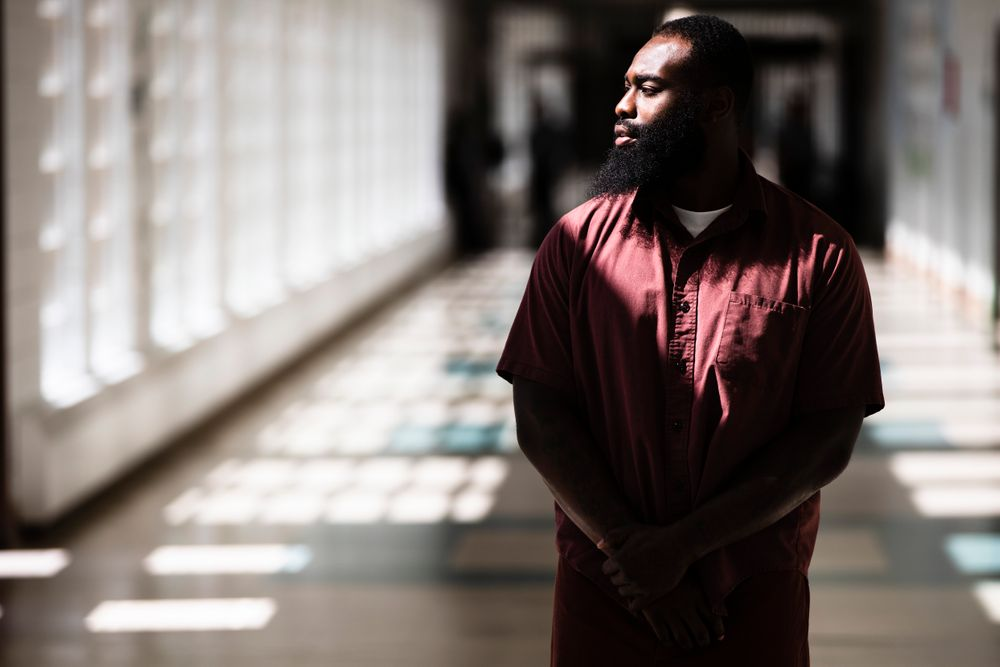 """In this Thursday, Aug. 29, 2019 photo, incarcerated filmmaker Robert poses for a portrait at the State Correctional Institution in Chester, Pa. Eastern State Penitentiary, a former prison that's now a museum in Philadelphia is showcasing the work of currently incarcerated filmmakers, projecting the animated shorts onto its outside walls. The new exhibit titled """"Hidden Lives Illuminated"""" offers a glimpse into the lives of these inmates to passersby and museum visitors alike.  (AP Photo/Matt Rourke)"""