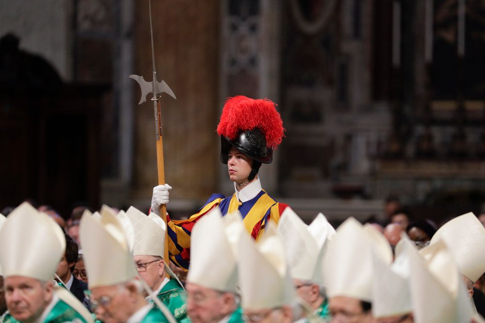 A Swiss guard stands attention as prelates attend an opening Mass for the Amazon synod, in St. Peter's Basilica, at the Vatican, Sunday, Oct. 6, 2019. Pope Francis is opening a divisive meeting on preserving the Amazon and ministering to its indigenous peoples, as he fends off attacks from conservatives who are opposed to his ecological agenda. (AP Photo/Andrew Medichini)