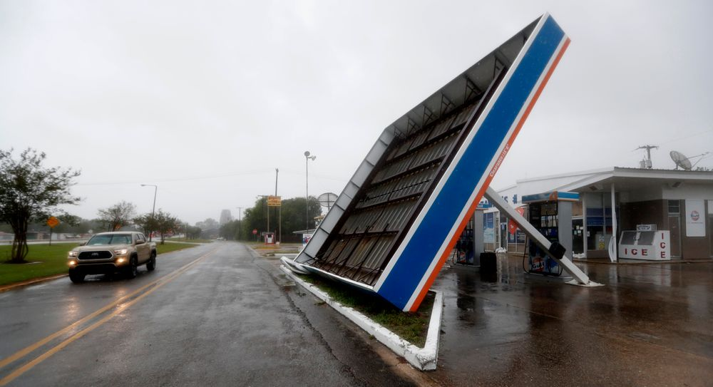 A vehicle passes a toppled gas pump canopy in Berwick, La., following a severe weather assault from Tropical Storm Barry, Saturday, July 13, 2019. (AP Photo/Rogelio V. Solis)
