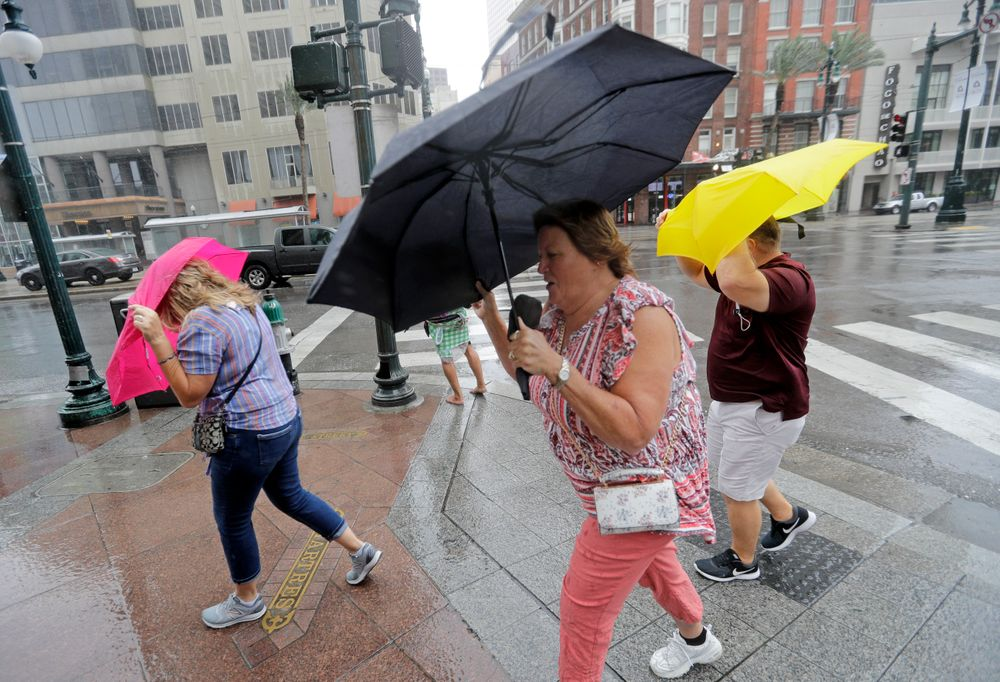Martha Young, center, Patricia Plishka, left, and her husband Glen, right, battle the wind and rain from Hurricane Barry as it nears landfall Saturday, July 13, 2019, in New Orleans. (AP Photo/David J. Phillip)