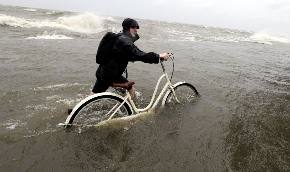 Tyler Holland guides his bike through the water as winds from Tropical Storm Barry push water from Lake Pontchartrain over the seawall Saturday, July 13, 2019, in Mandeville, La. (AP Photo/David J. Phillip)