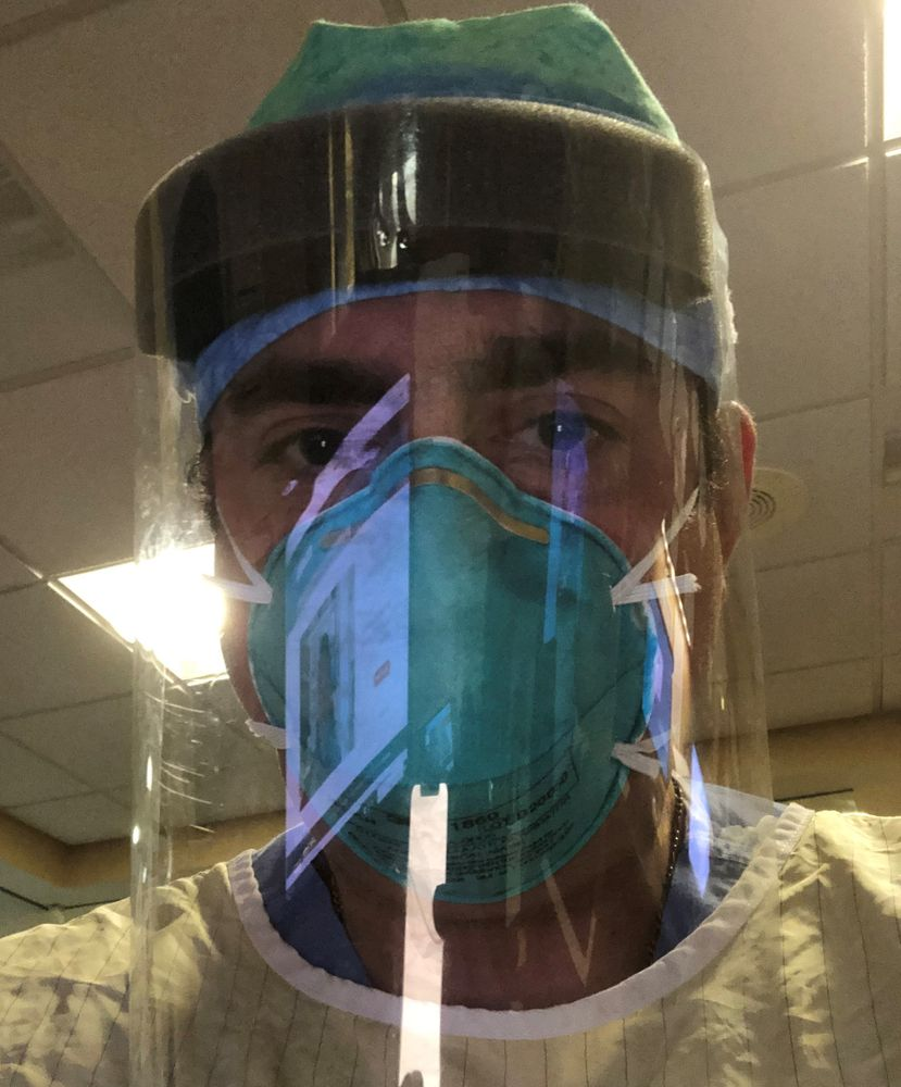 Dr. Joseph Lauro puts on an N95 mask and face shield to work in the emergency department