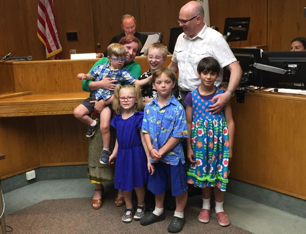 Ally, Matt, and their five kids pose for a picture after their adoption is finalized.