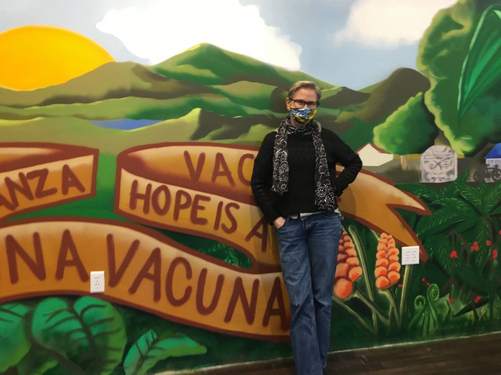 Dr. Annie De Groot, volunteer medical director at Clinica Esperanza, in front of a mural at the storefront clinic on Valley Street in Providence, R.I.