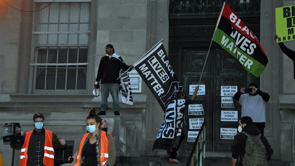 Protesters are pictured at a rally Tuesday night outside Knight Memorial Library in Providence.