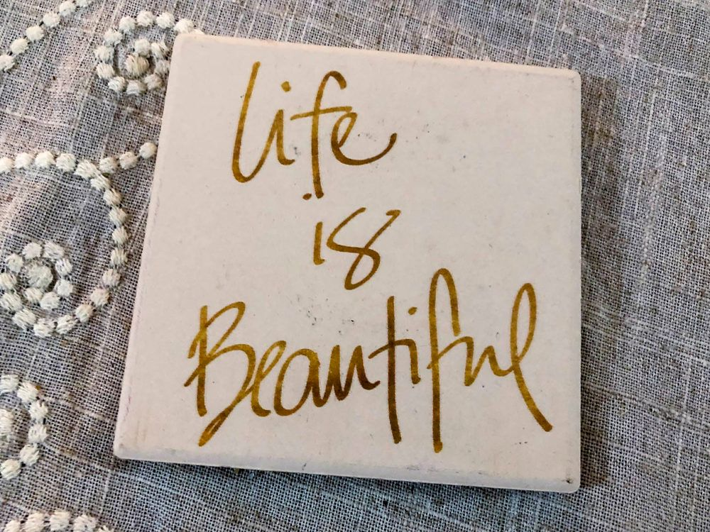 "Coasters on the table where the support group meets say ""Life is Beautiful"" and ""Laugh Often."""