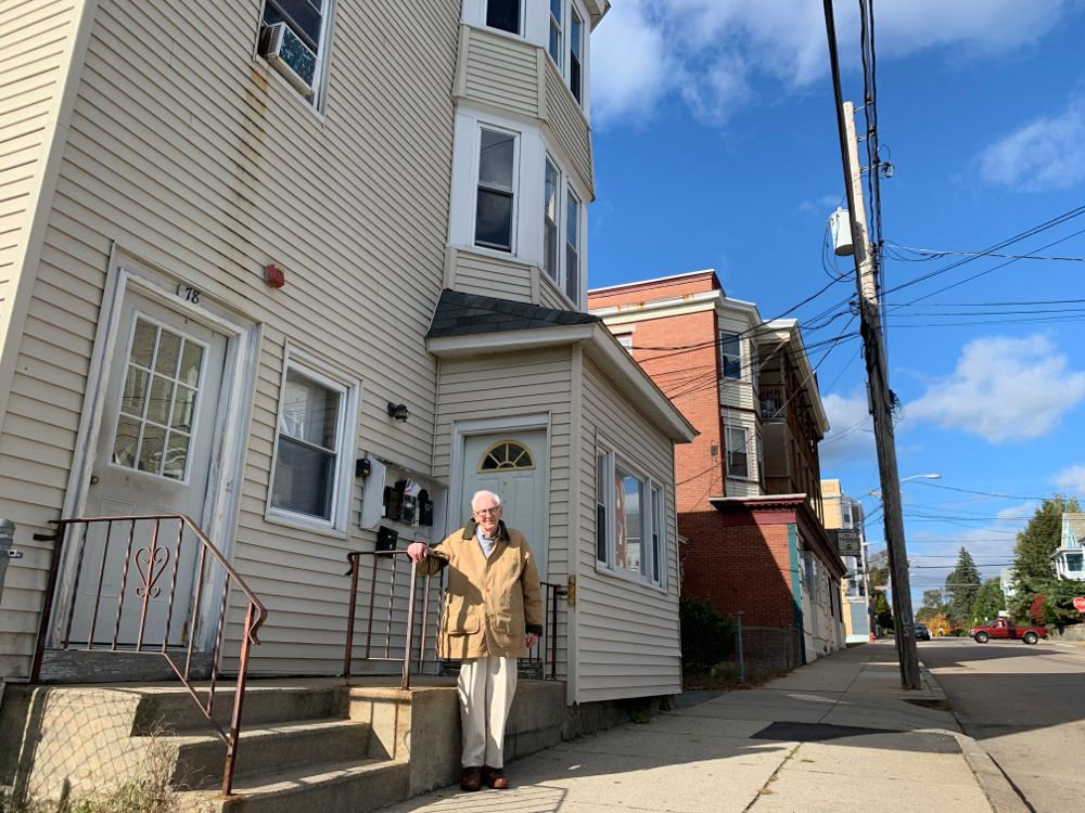 Gene Peloquin outside of the triple decker his mother moved into not long after arriving in Woonsocket from Canada