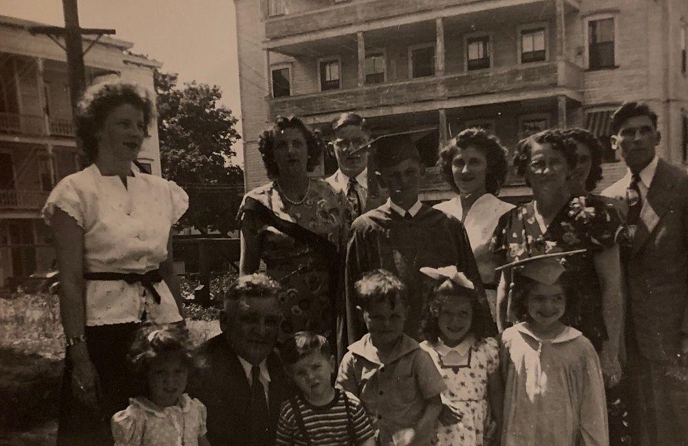 Gene Peloquin, center in graduation gown, in his family's old triple decker neighborhood.