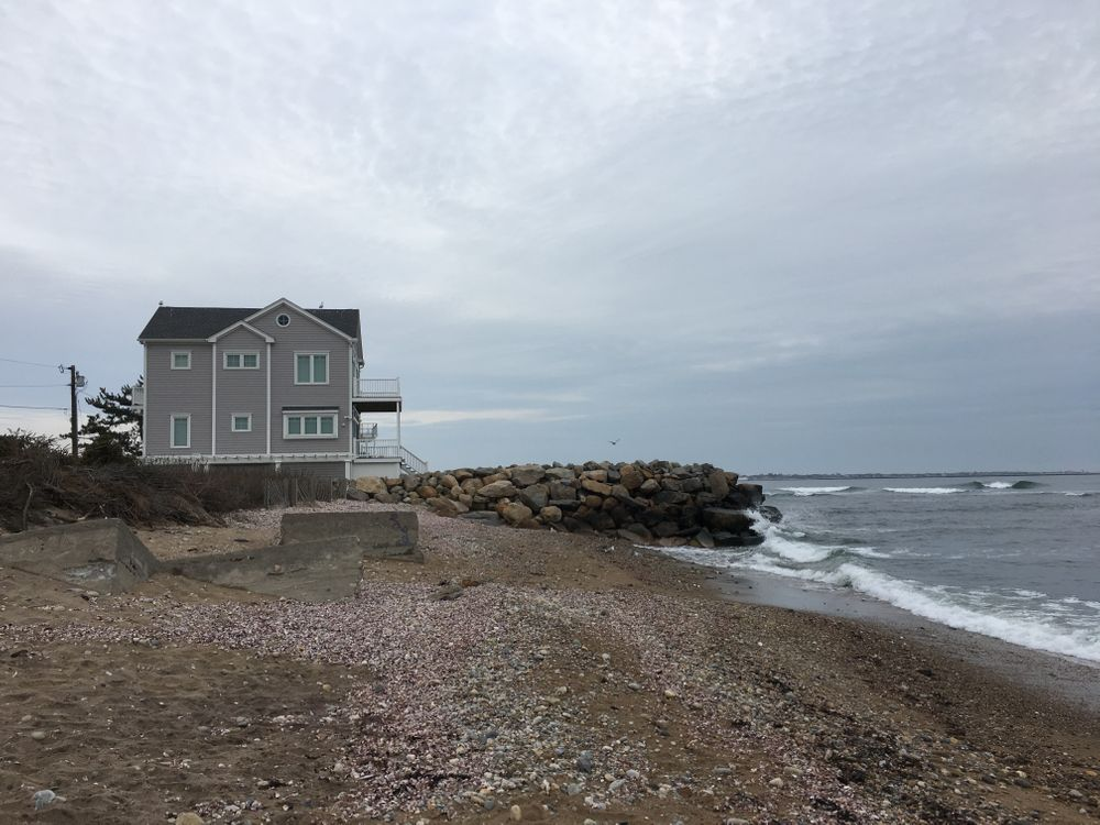 The beach at Deep Hole is eroding, while a stone wall protects a nearby home.