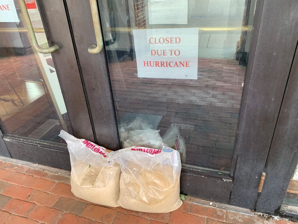Sandbags sit outside the closed Museum of Newport History gift shop on Thames Street Sunday in Newport, R.I.